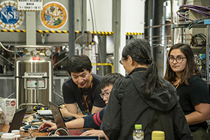 Li (far left) and other members of Cory Dean's research group conduct an experiment on graphene.