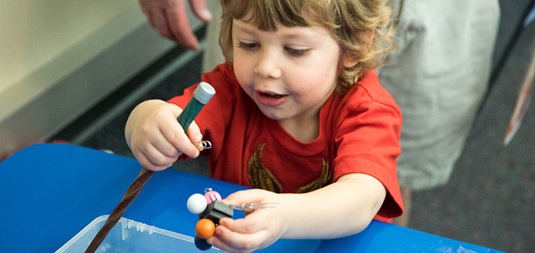 Child exploring with magnets.
