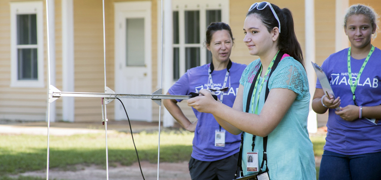 A SciGirl uses a radio antenna during a field trip at Tall Timbers Research Station to search for banded birds