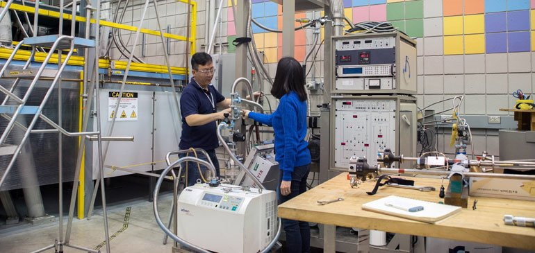 MagLab physicists Ju-Hyun Park (left) and Hongwoo Baek install the portable dilution refrigerator.