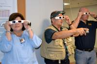 Scientist Bob Goddard (center) and two of the teachers he mentored use 3-D glasses to examine images outside his lab.