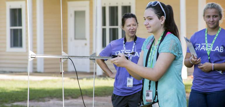 A SciGirl uses a radio antenna during a field trip at Tall Timbers Research Station to search for banded birds.