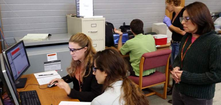Patricia Medeiros (far right) watches data from her experiment with her grad students.