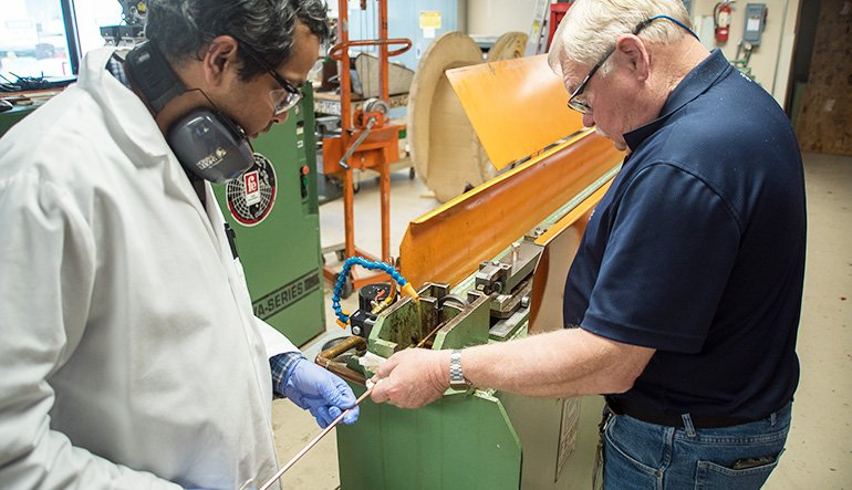 Research scientists Shreyas Balachandran (left) and William Starch draw lengths of niobium-tin superconducting wire at the Applied Superconductivity Center at the National High Magnetic Field Laboratory. A new grant of $1.5 million will allow the group to continue this research.