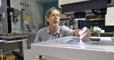 Research Associate Bob Walsh examines  the fracture surface of a tensile specimen on an inspection microscope in the Mechanical and Physical Properties Lab.