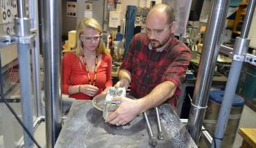 High school senior Rachael Steverson with mentor Adam Voran in the materials testing lab.